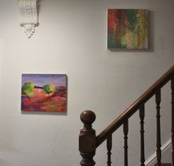 The stairs to the first floor, with paintings by Alison Litherland and Kate Green