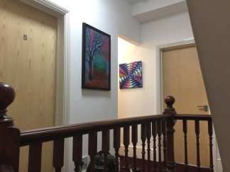 The first floor landing, with original paintings by Chris Langley and Ruth Hawkins