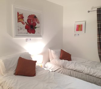 Twin bedroom, with limited edition prints by Gerry Wilmer and Kate Green